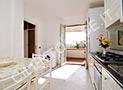 La cucina attrezzata con tv, frigo, lavatrice e terrazzino