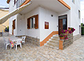 L'esterno con tavolo attrezzato e l'ingresso all'appartamento Grazia