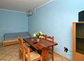 Il tavolo da pranzo, il divano letto e la tv dell'appartamento Le Acacie Comfort