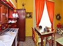 Veduta d'insieme della sala da pranzo con tv, divano e cucina