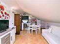 Gli interni della mansarda e in fondo il soggiorno con divano letto, tv e cucina attrezzata