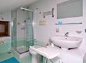 Il bagno con box doccia, lavatrice e lavatoio