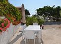 Esterno arredato con tavolo, sedie e ombrellone appartamento Scirocco