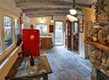 Panoramica del soggiorno con tavolo, sedie, camino e cucina