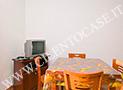 Il tavolo, la tv e un angolo del terrazzo dell'appartamento Parmenides