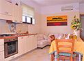 Camera da pranzo con cucina attrezzata di lavastoviglie, frigo e macchina per espresso Appartamento Magna Grecia