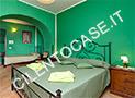 La camera in tinta verde con letto matrimoniale e letto singlo dell'appartamento Natura