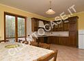 La sala da pranzo con il grande tavolo e la cucina dotata di forno elettrico, lavastoviglie e cappa